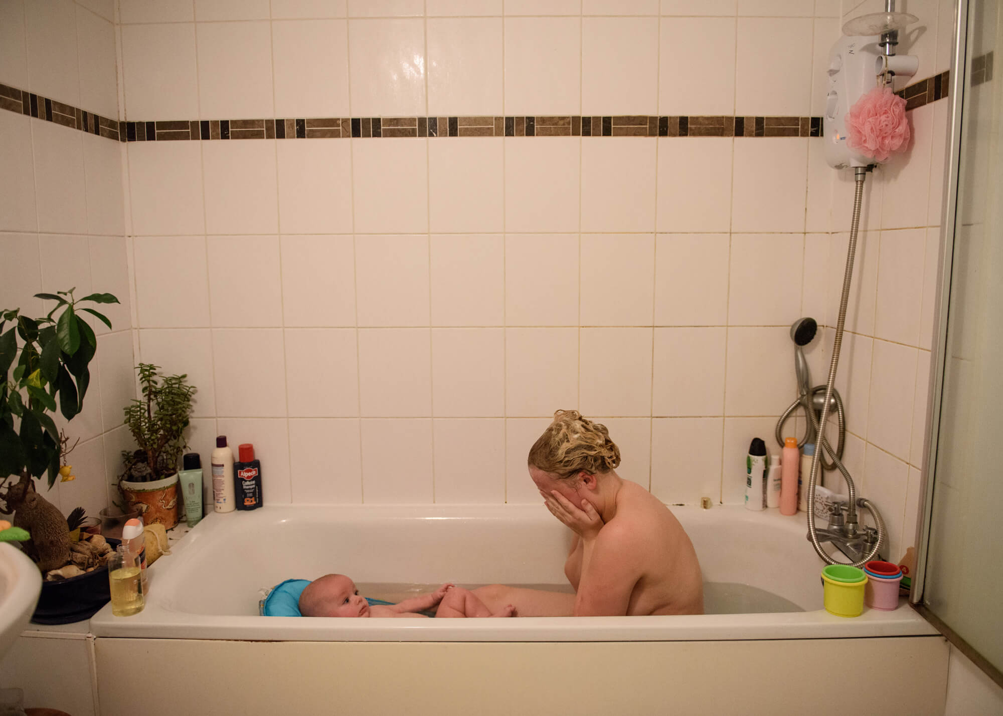 Alice Dempsey photography goodnight god bless women sat naked in bath washing her small baby with white tiled background the south west collective of photography