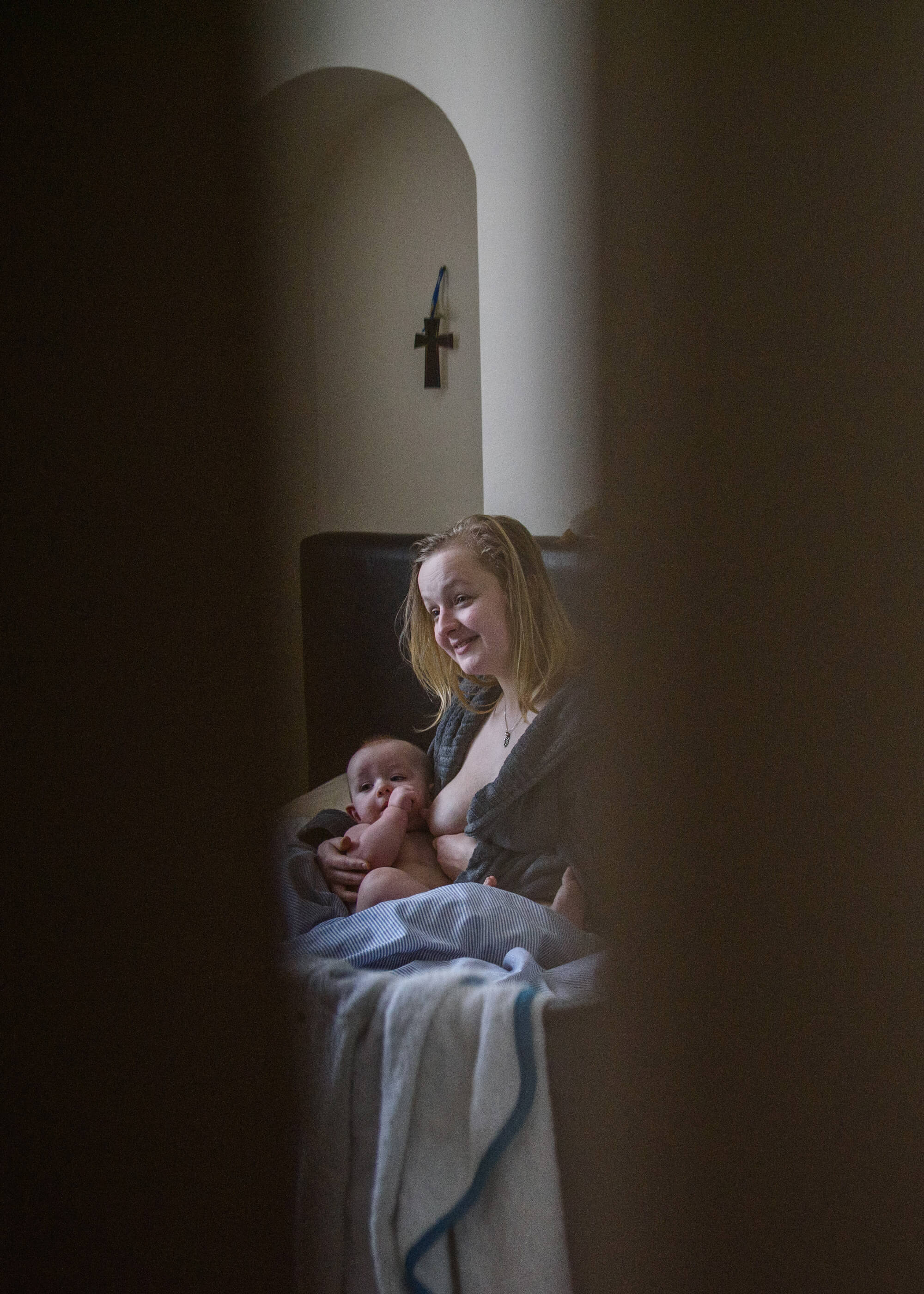 Alice Dempsey photography goodnight god bless women breastfeeding her baby on sofa the south west collective of photography ltd
