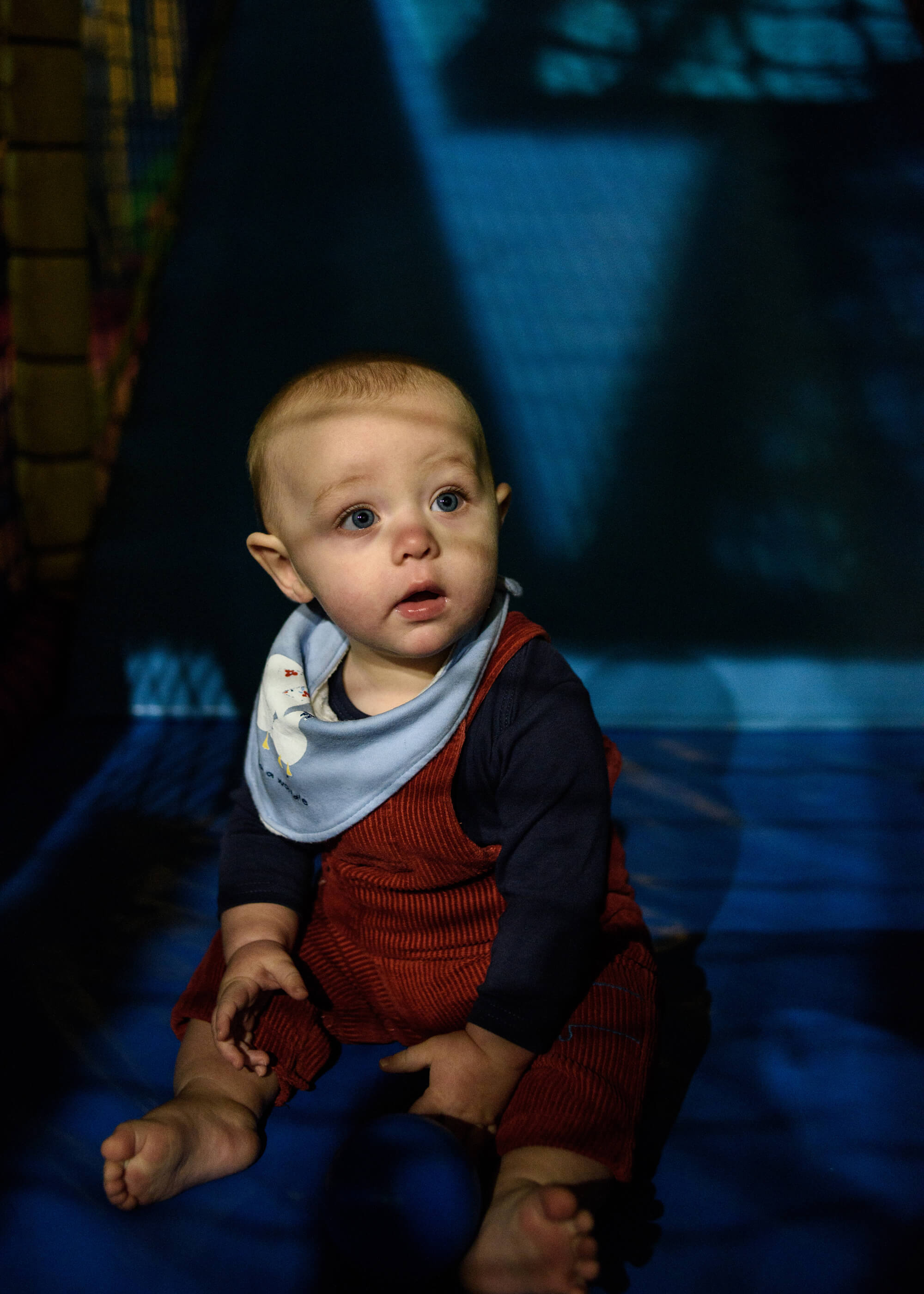 Alice Dempsey photography goodnight god bless baby playing on floor with blue background the south west collective of photography ltd