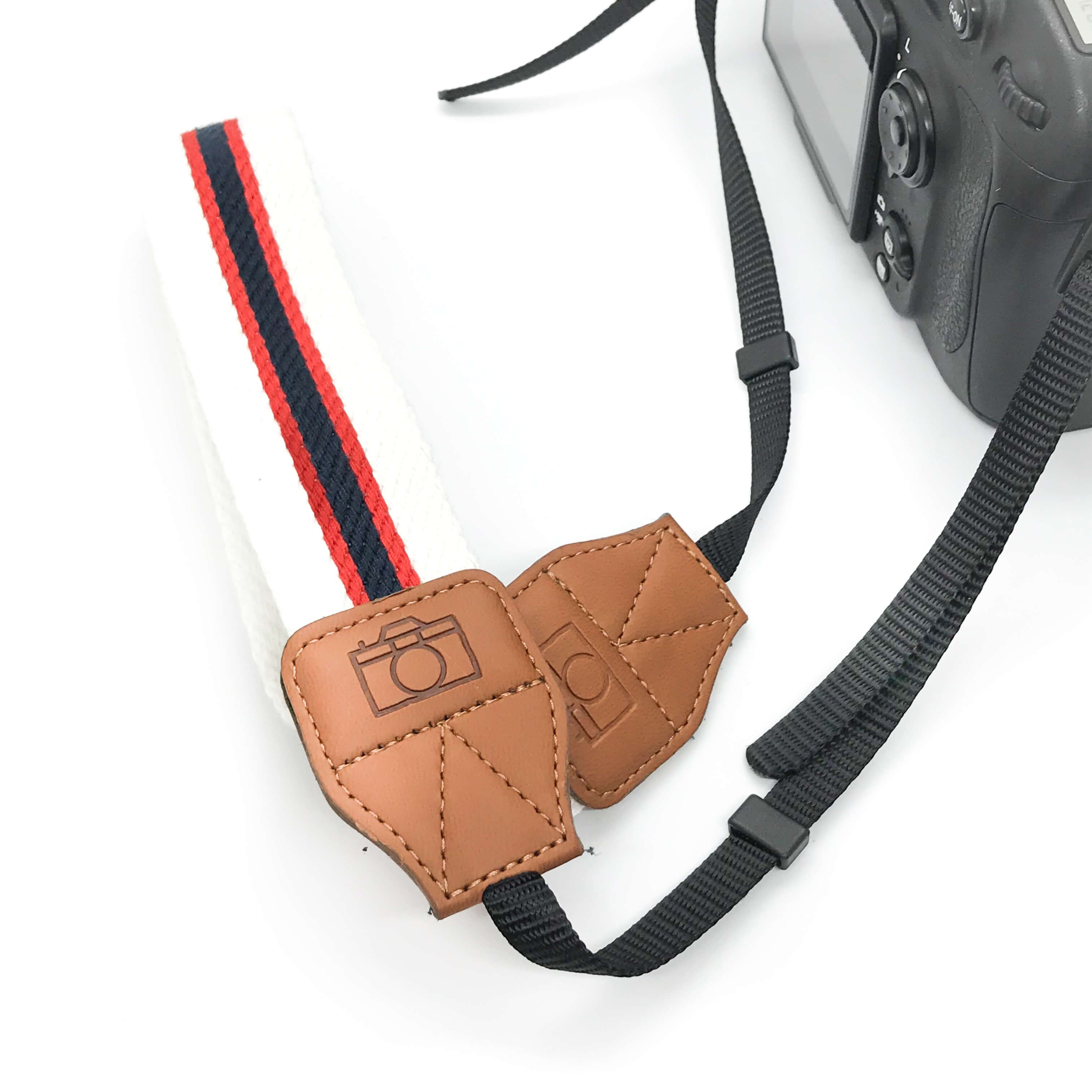 Black Red and White Camera strap on white background with camera
