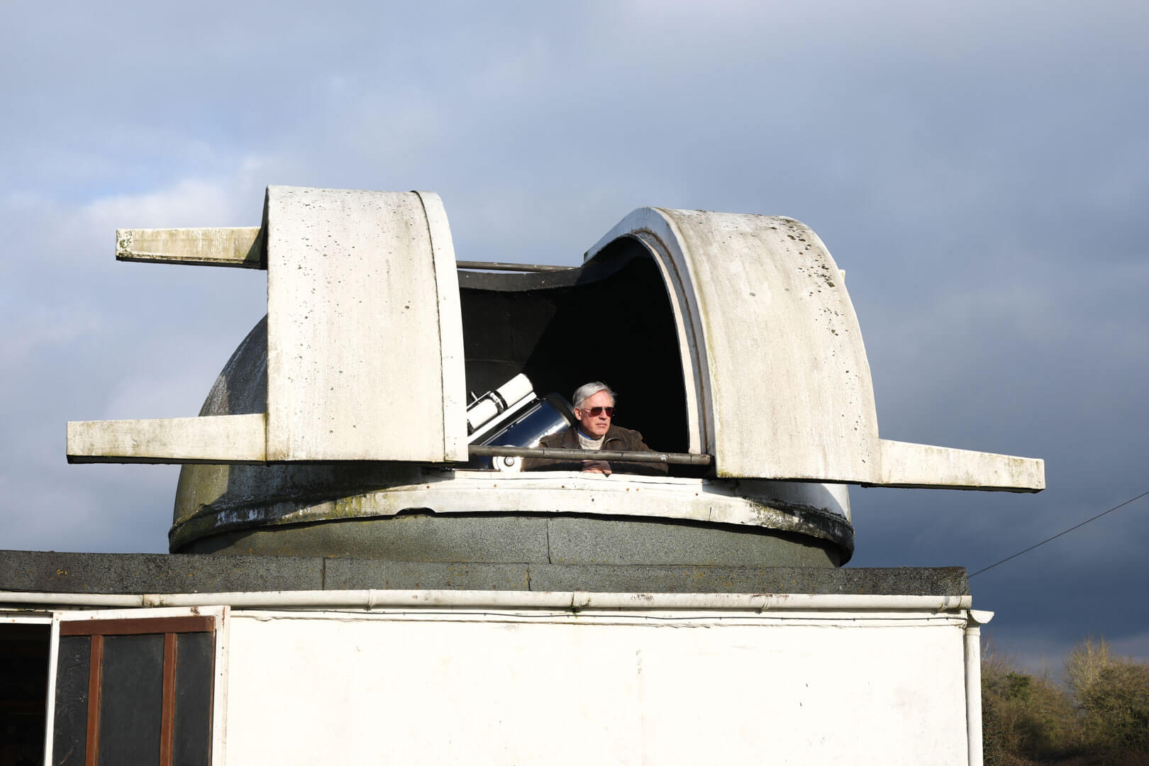 man looking out of his home made telescope