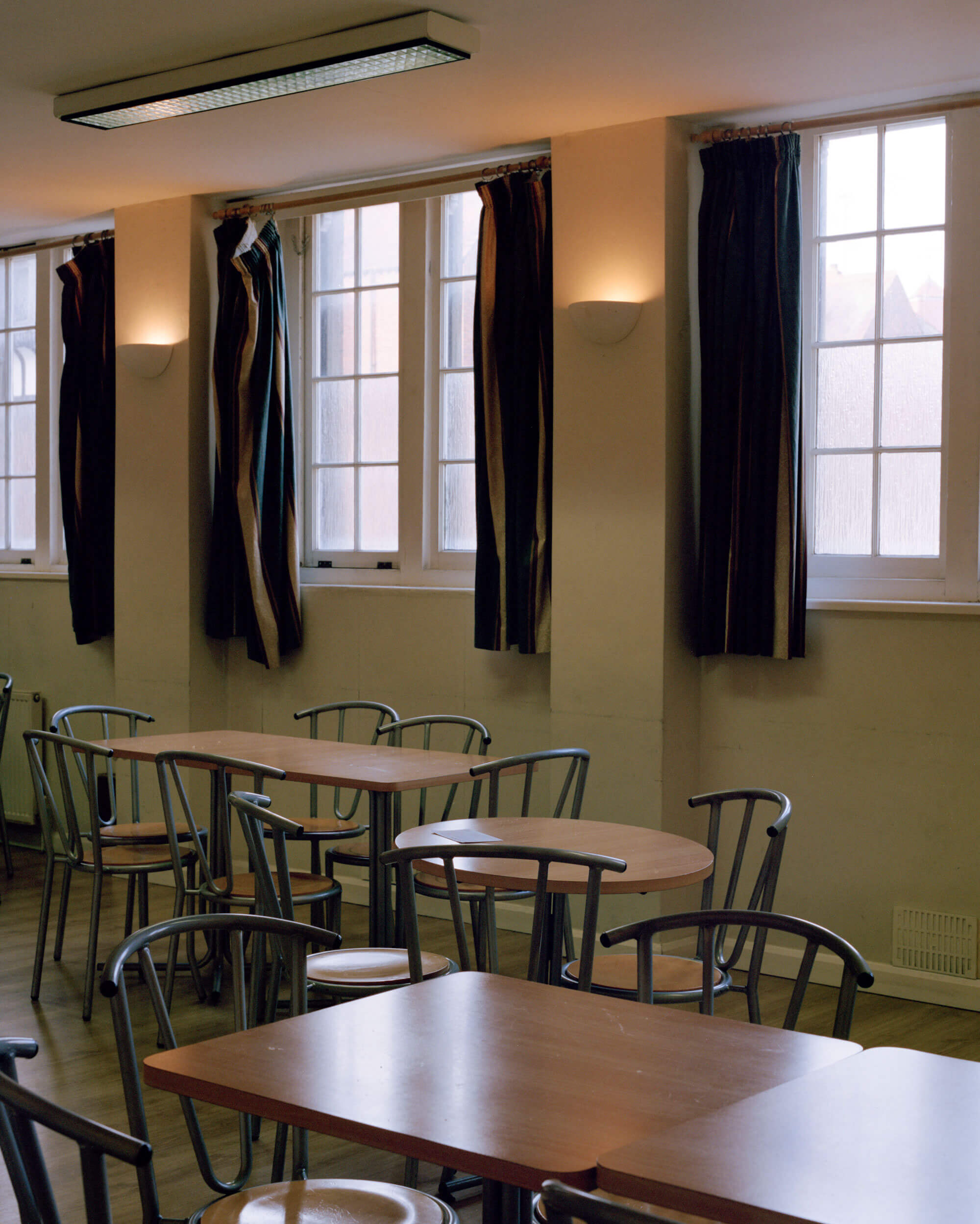 church mess hall in daylight with lights on and red curtains