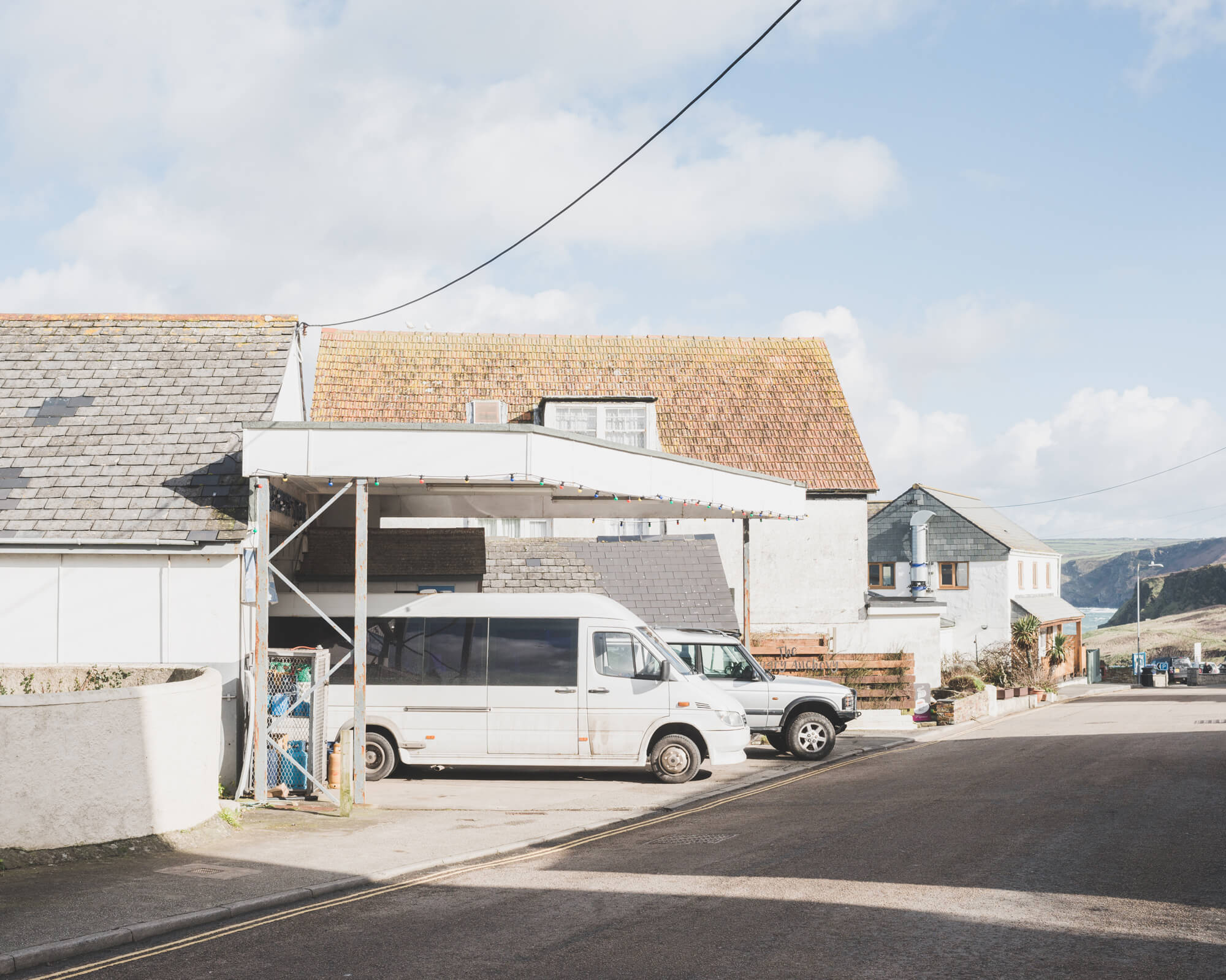 mini buses parked under shelter in Cornwall with sunlight on them and blue sky rob hardy