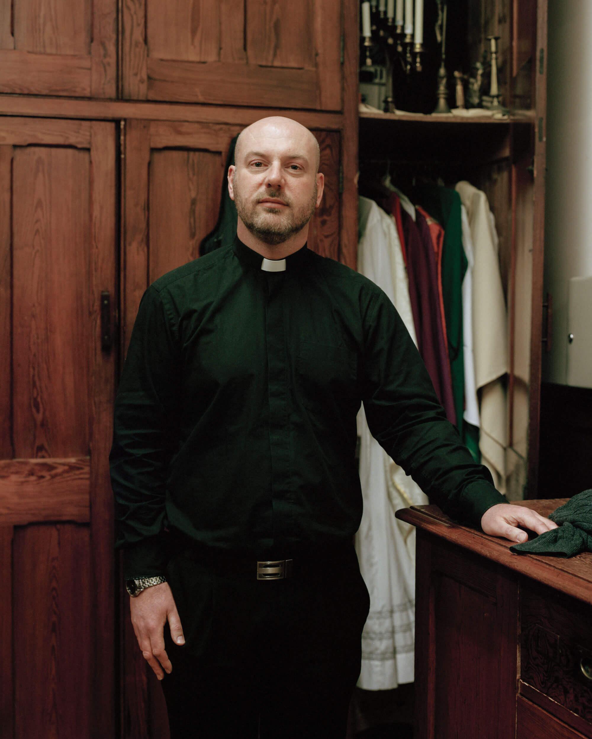 Father ross stood in church robes next to a wardrobe in a Catholic Church matt Scott