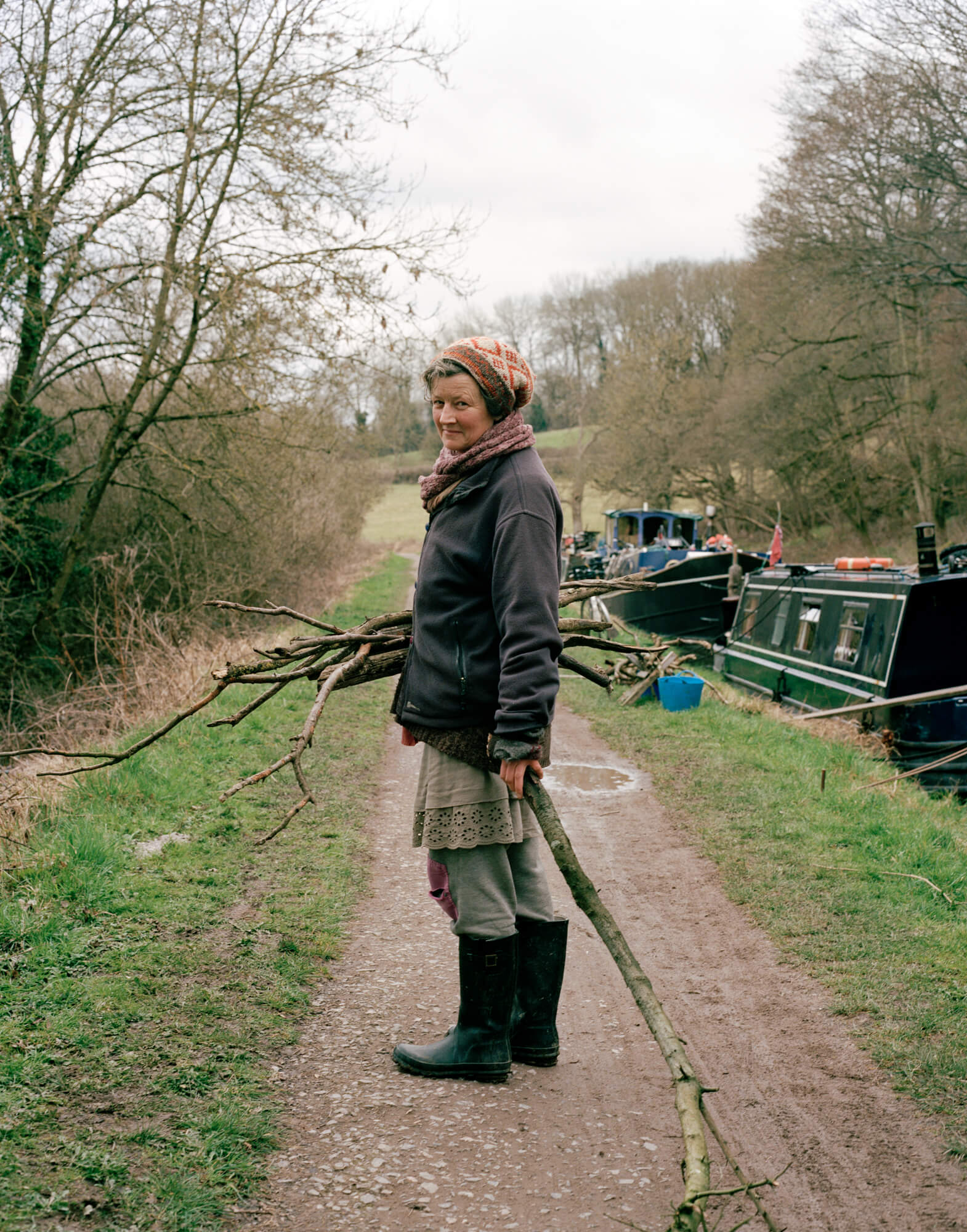 women stood next to canal boat holding logs next to river on green background