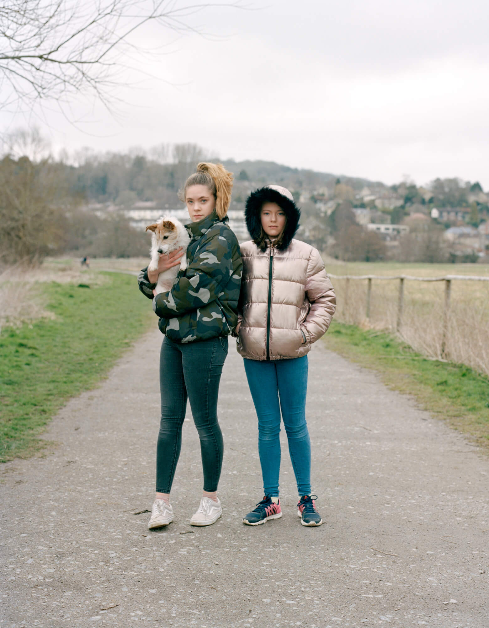 Two girls stood on path with a grey background by a river in a park