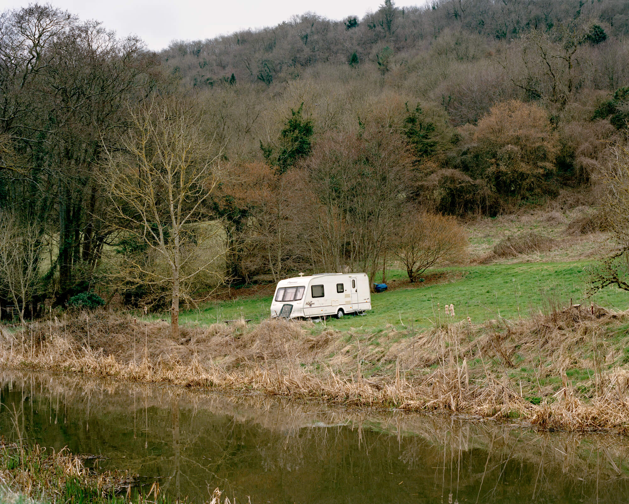 caravan in a field next to a river on a grey day with green and brown background Ella cousins river