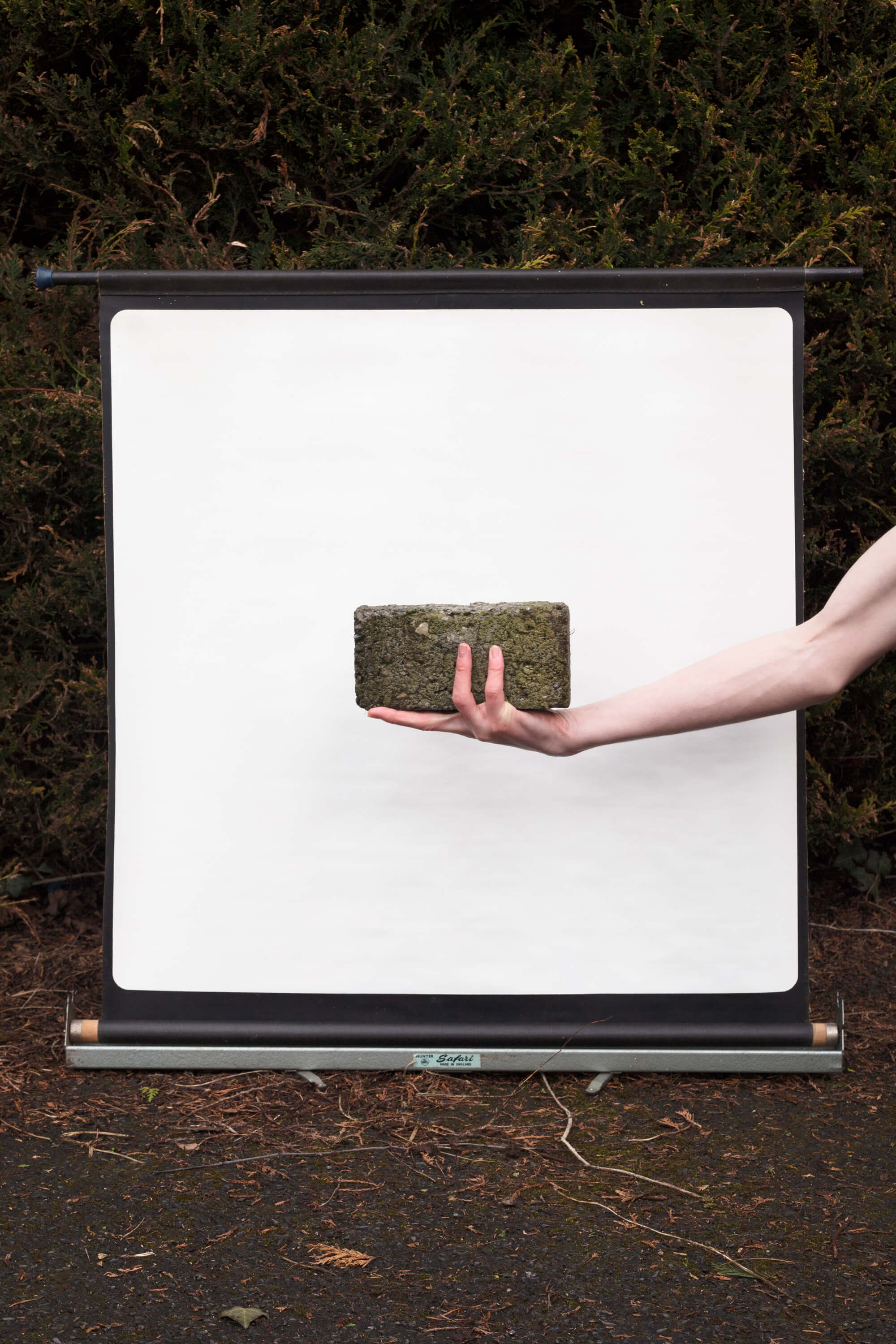 man holding brick in garden against white background on the south west collective of photography