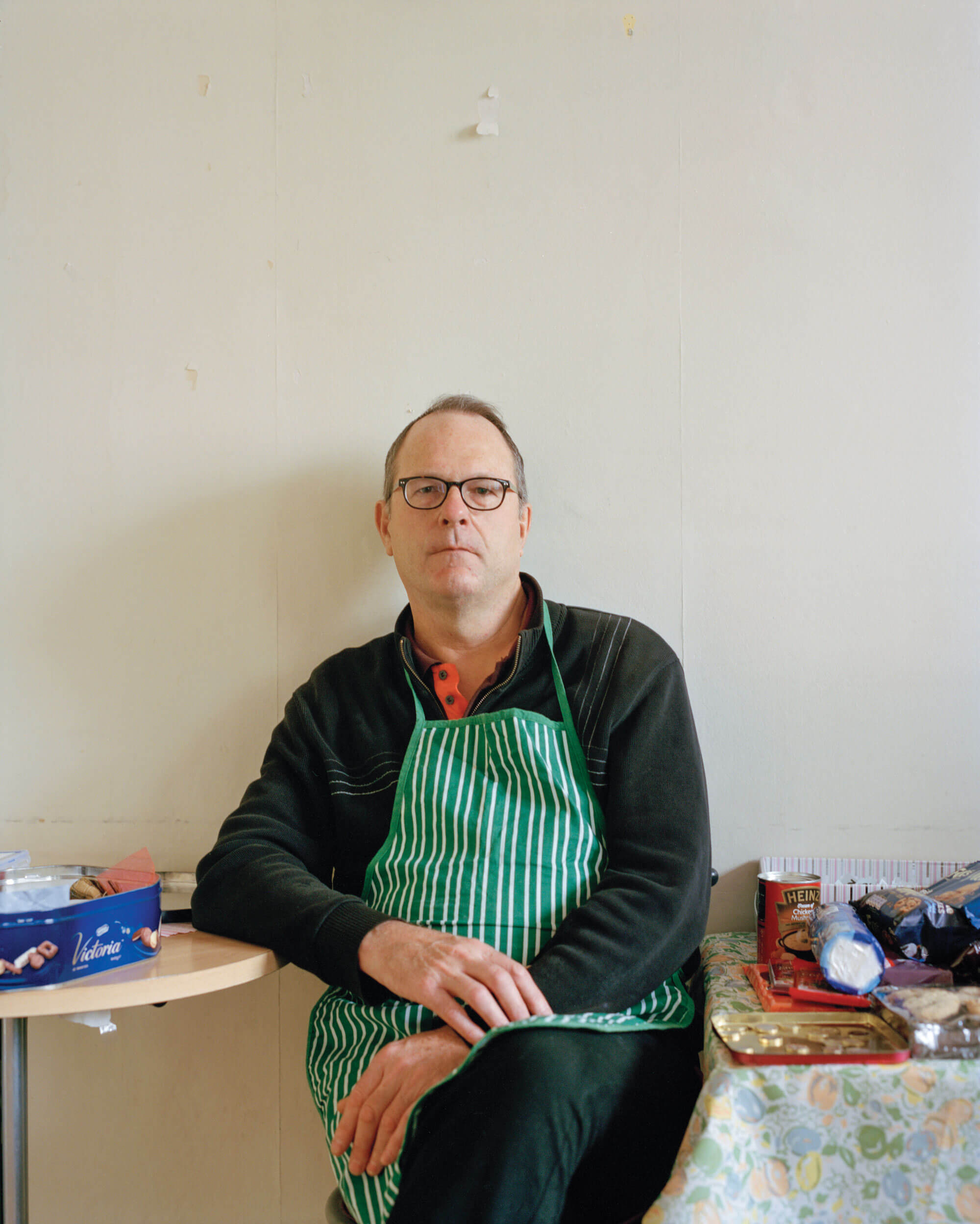 man sat in green apron against white wall in Catholic Church