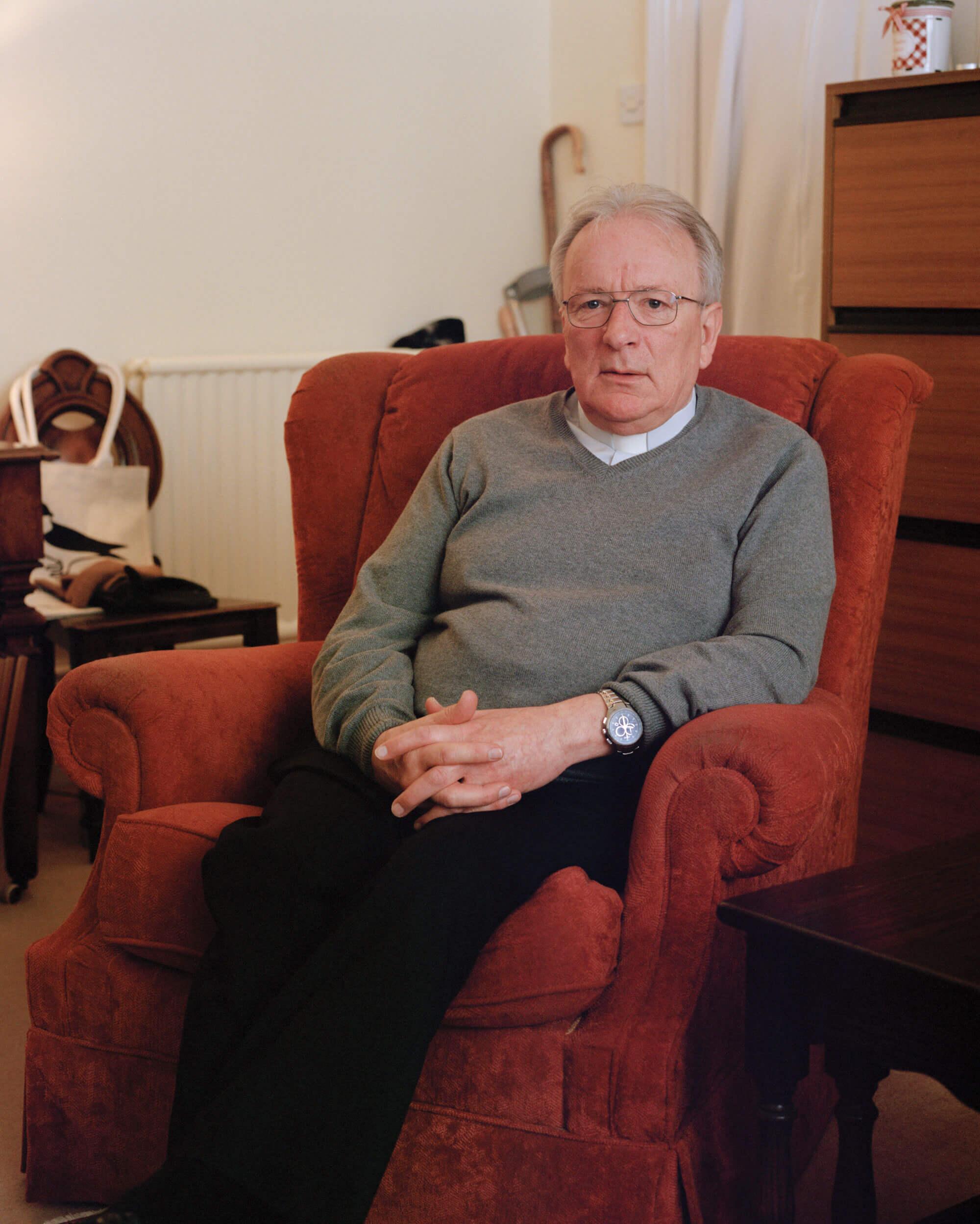 man sat in red chair against white wall in a Catholic Church by matt Scott