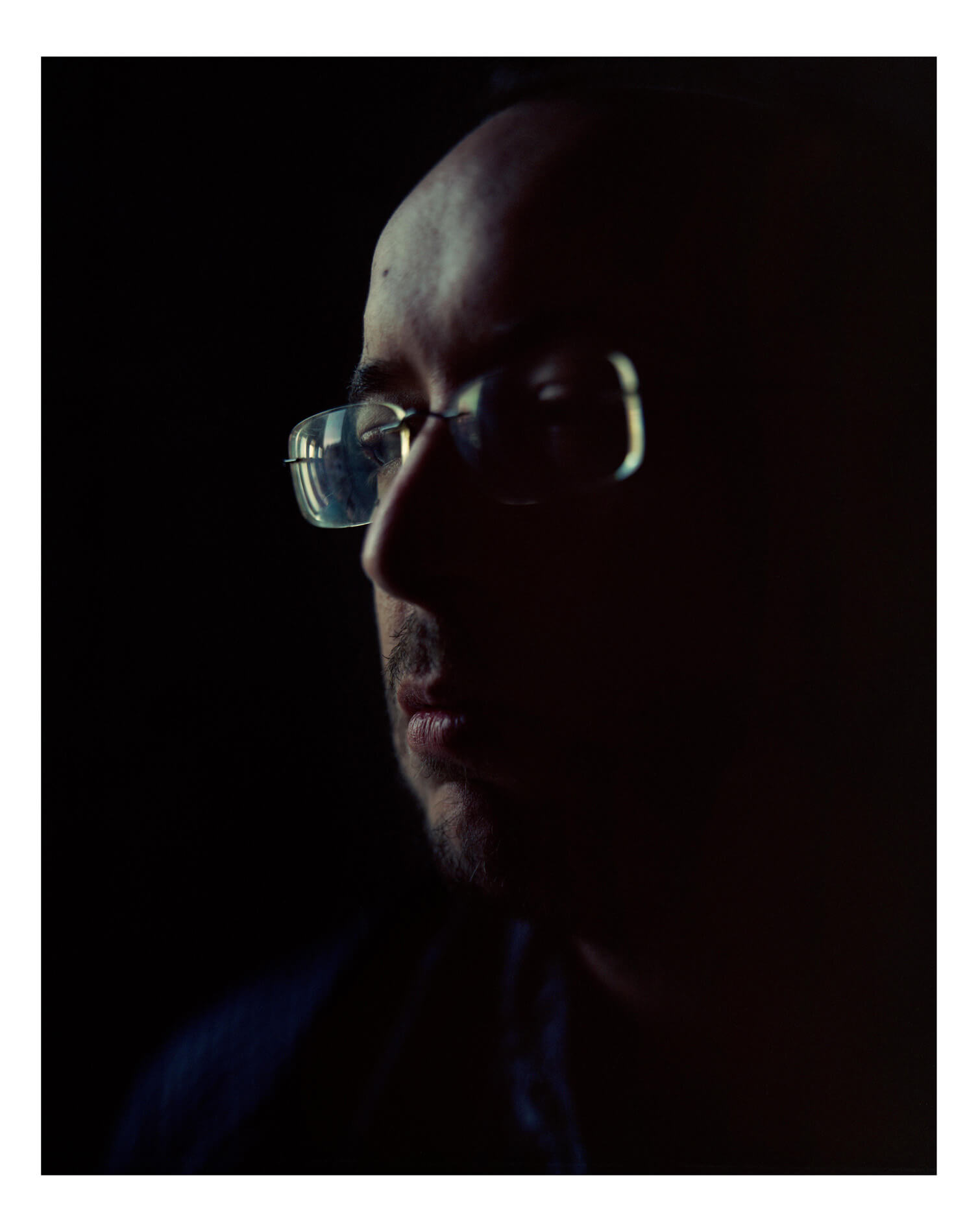 mans face in low light with black background reflecting of glasses