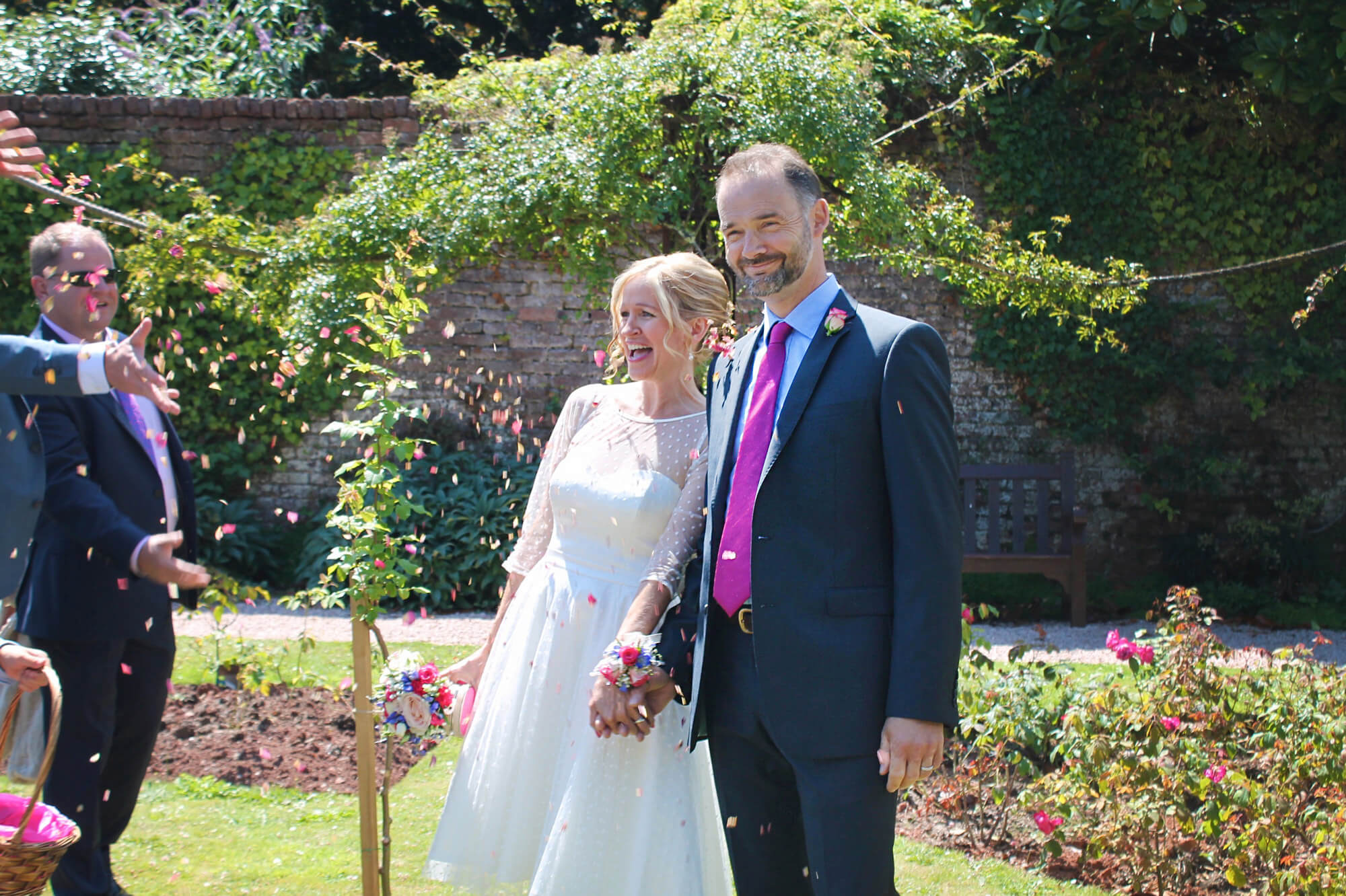 A couple newly married in a garden on a sunny day