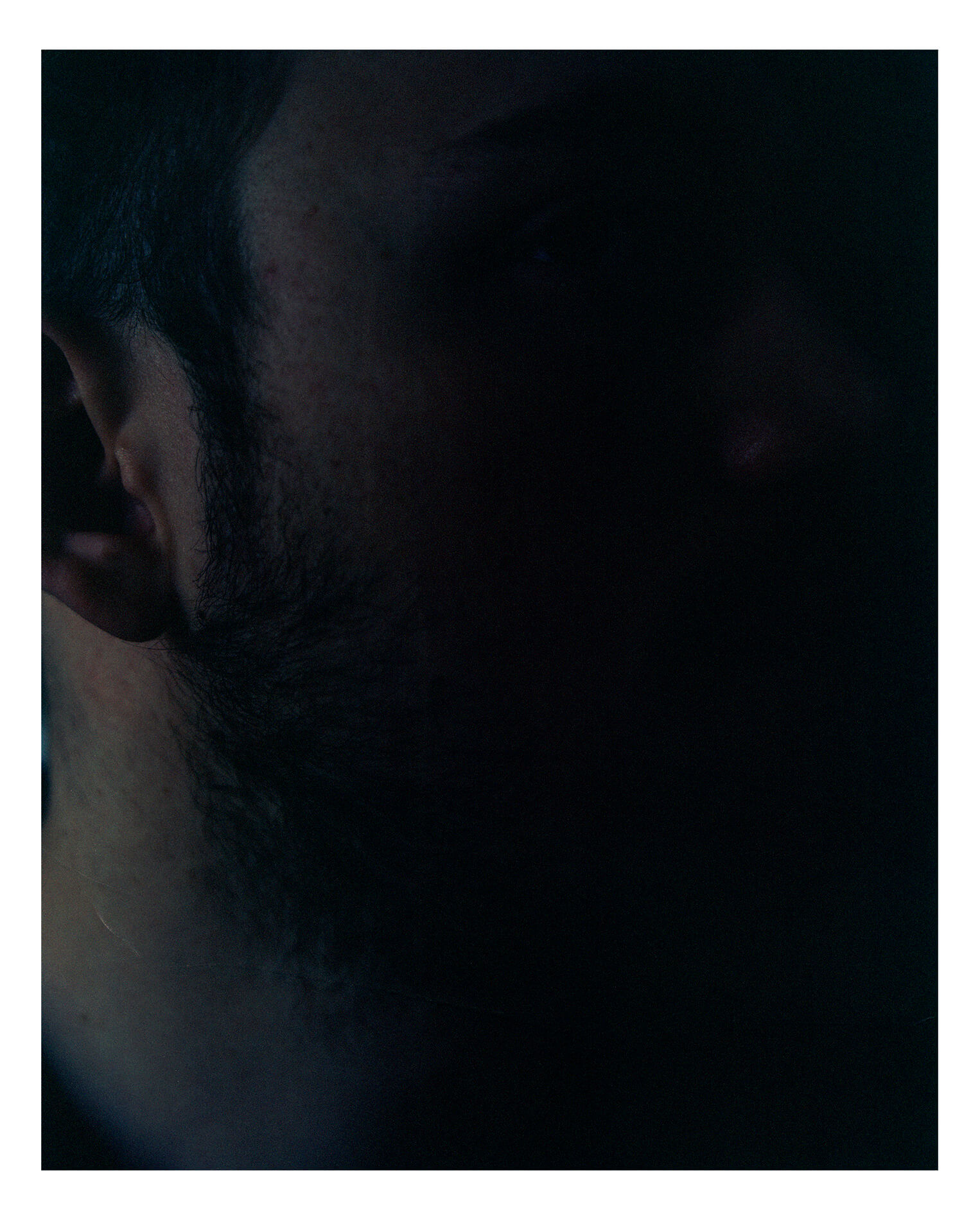 mans face in low light with black background