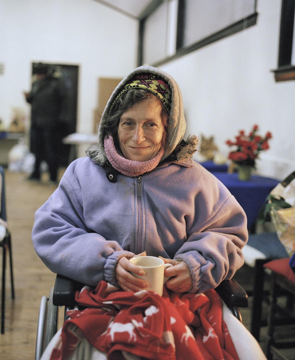 Sandra Mickiewicz Happy Club stabled women sat in wheelchair in village hall drinking tea