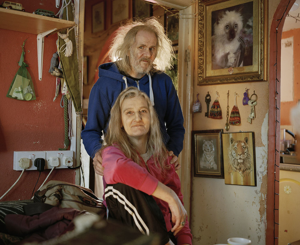 Sandra Mickiewicz Happy Club couple sat in their home with photos and ornaments in the background
