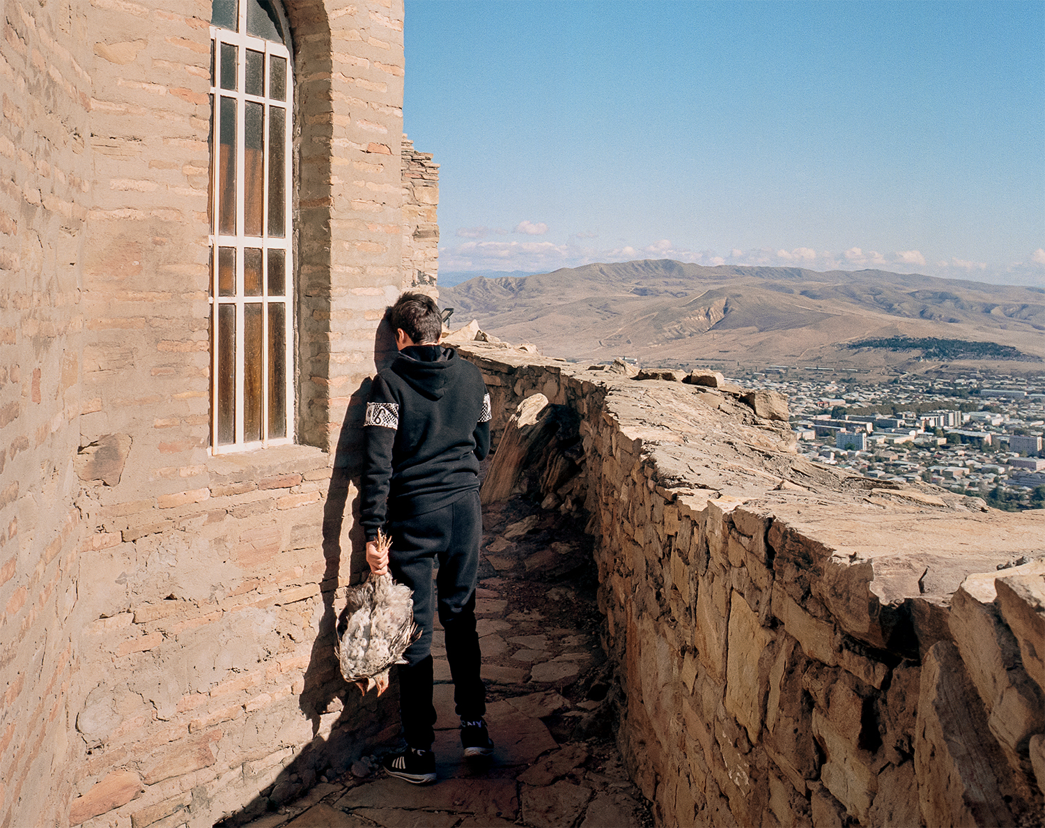 Steffen Junghanß The Invisible Border man stands facing wall overlooking town and mountains
