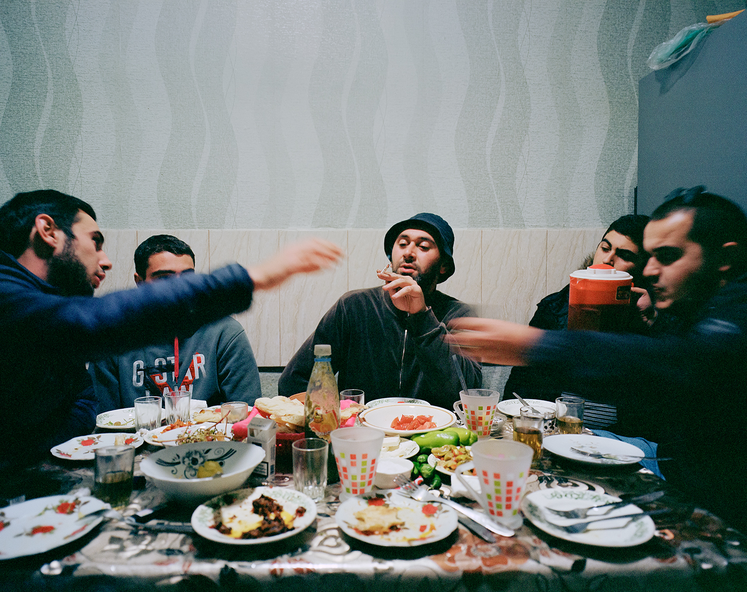Steffen Junghanß - The Invisible Border group of boys smoke and eat dinner together