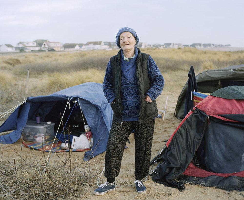 Sandra Mickiewicz Happy Club lady stood between three tents on a beach in jaywick