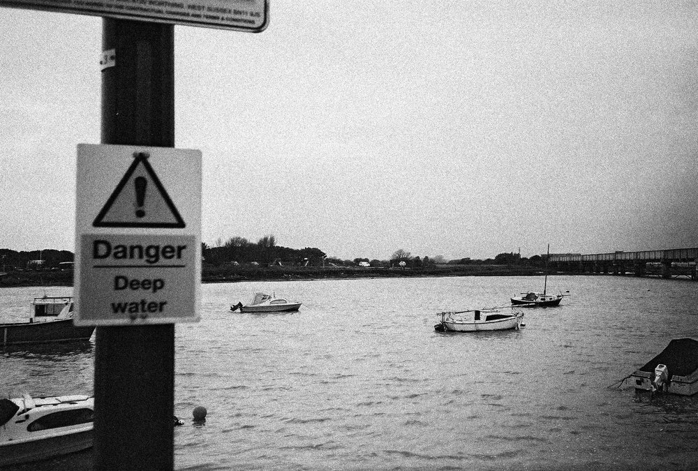 deep water warning sign next to mouth of a river