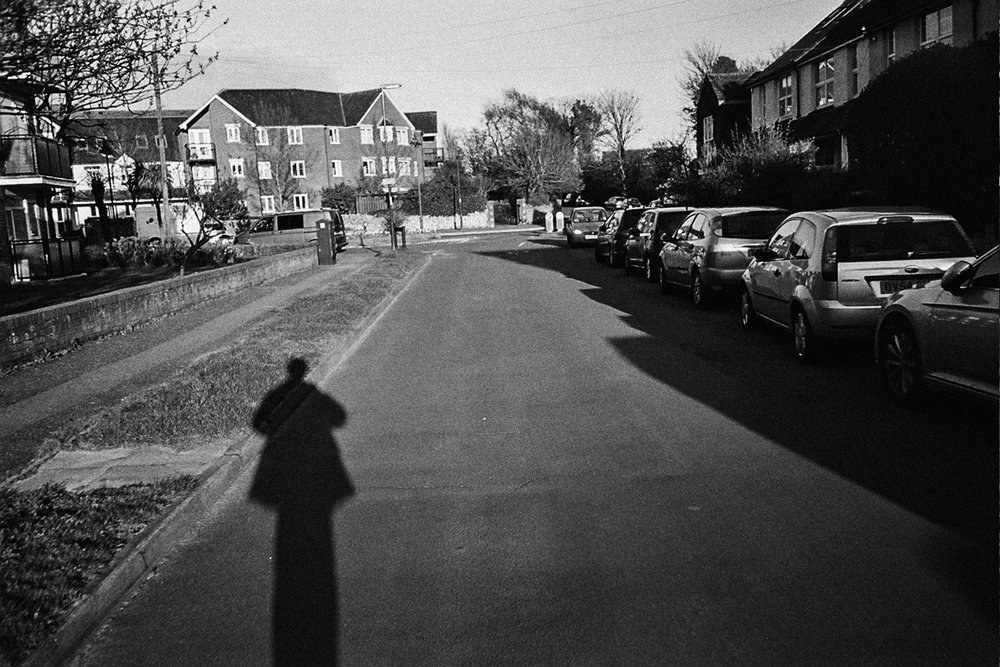 Shadow of strange man walking down the streets in black and white