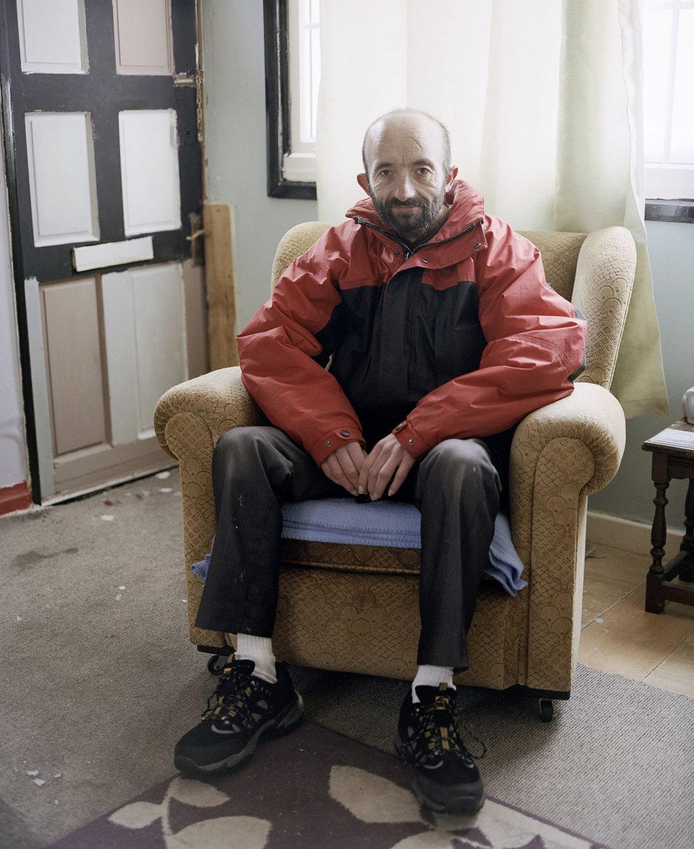 Sandra Mickiewicz Happy Club Man sat in chair in run down home