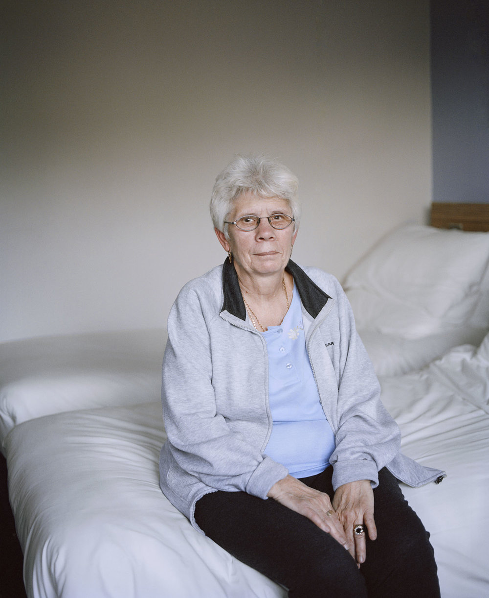 Sandra Mickiewicz Happy Club Pensioner sat on her bed against white background