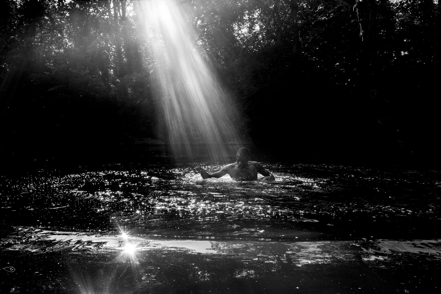 the south west collective Caleb stein man swimming in river while sun shines through trees