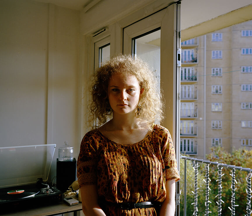 Portrait of girl with sunlight on her face in kitchen Imogen Glanville the south west collective of photography