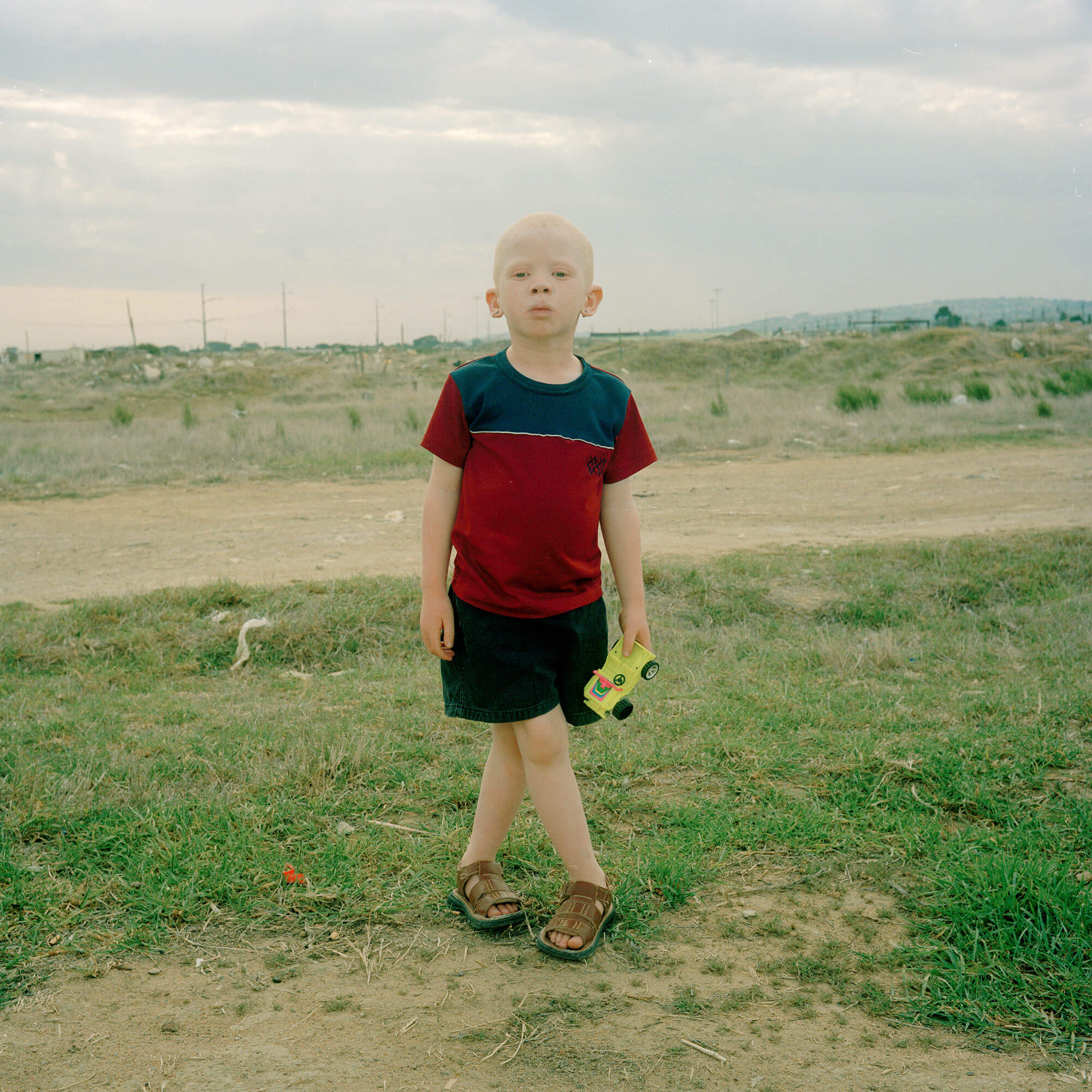 Claudio Rasano SOUTH AFRICA EVERYONE LIVE IN THE SAME PLACE LIKE BEFORE portrait of boy stood in field