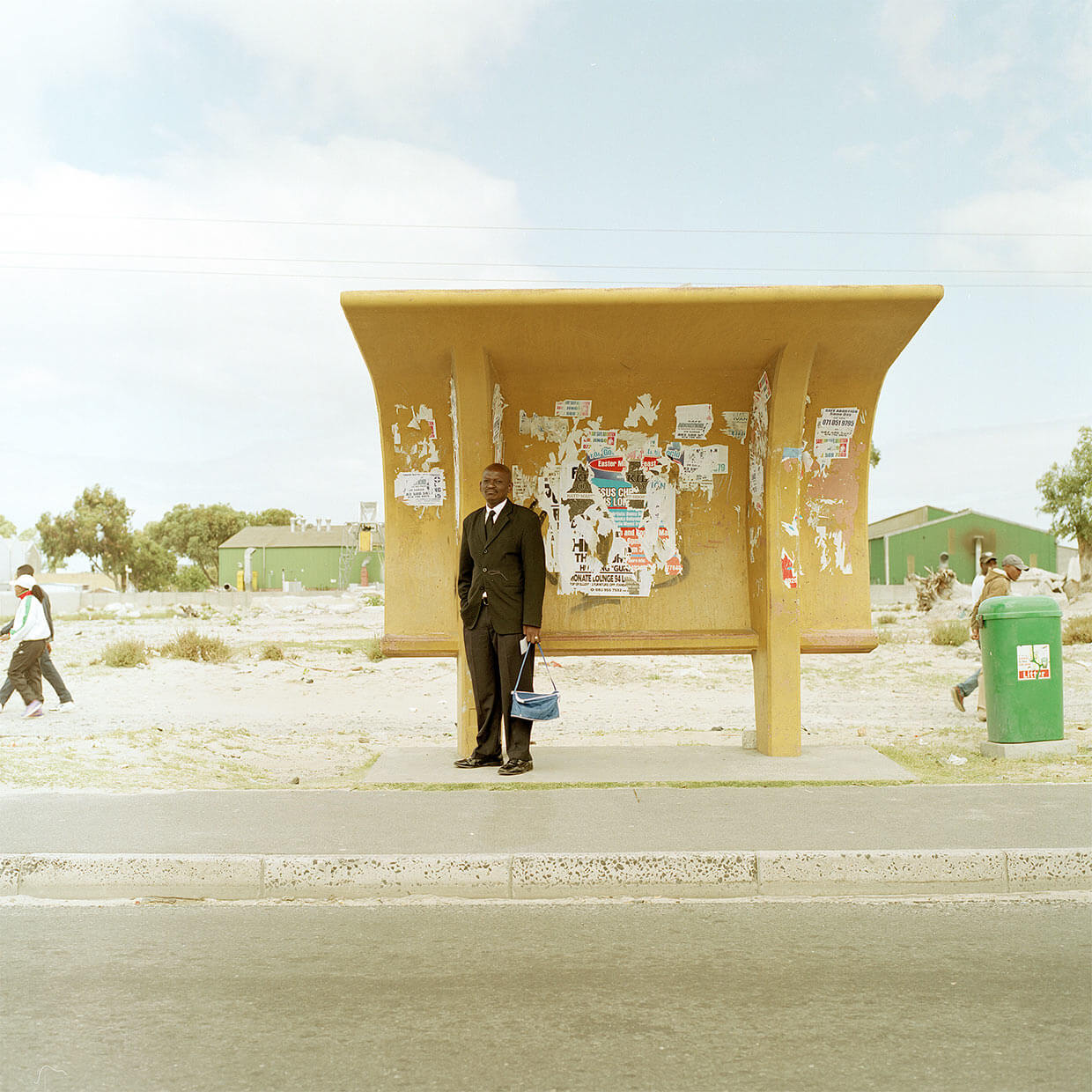 Claudio Rasano SOUTH AFRICA EVERYONE LIVE IN THE SAME PLACE LIKE BEFORE portrait of man waiting at bus stop