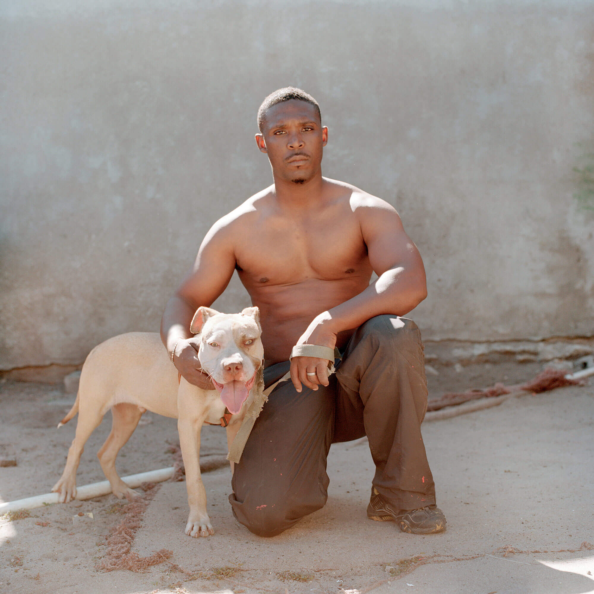 Claudio Rasano SOUTH AFRICA EVERYONE LIVE IN THE SAME PLACE LIKE BEFORE portrait of man and his dog in sunlight
