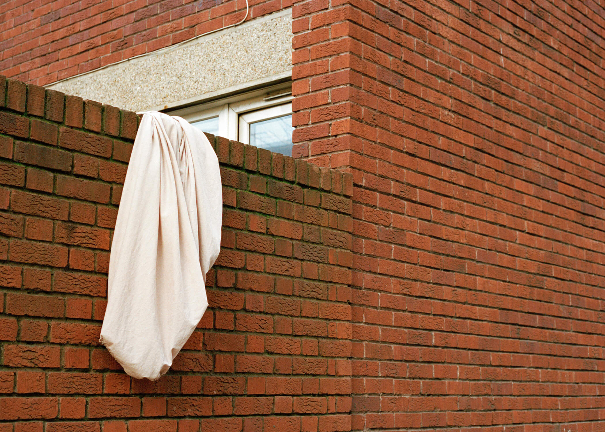 Skaidrė Rudokaitė - Ambivalence bed sheet hanging off red brick wall the south west collective