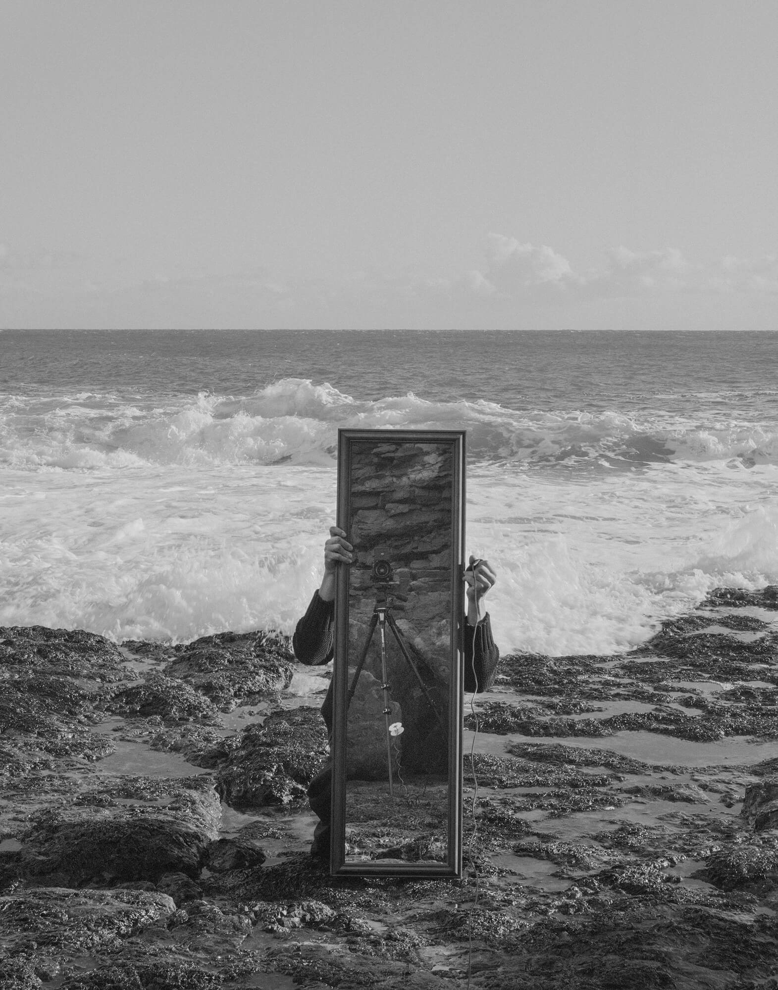 Ezra Evans - Untitled #5 the south west collective of photography man holding mirror on the rocks and the beach