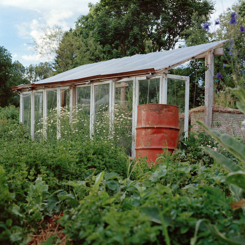 Kadri Otsiver - Ta aed on tema nägu (Her garden has her face) A greenhouse with plantation outside and an orange bin