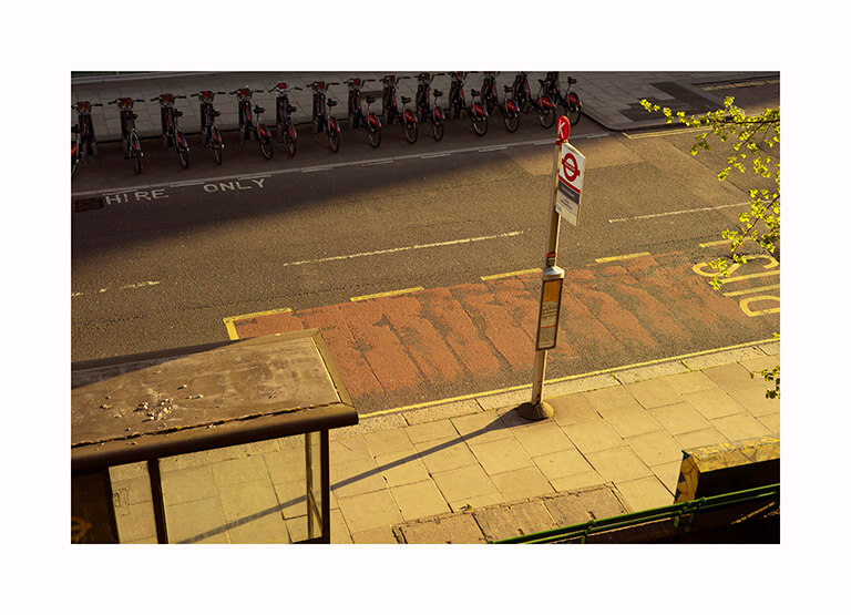 Kofo Olayanju - What Will Become of Us. Bus stop scene captured from above in golden light
