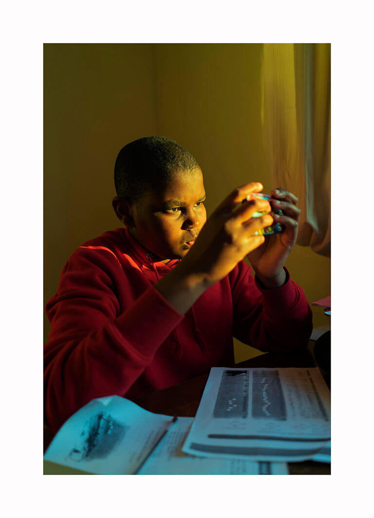 Kofo Olayanju - What Will Become of Us. Portrait of boy playing playing game console in golden sun