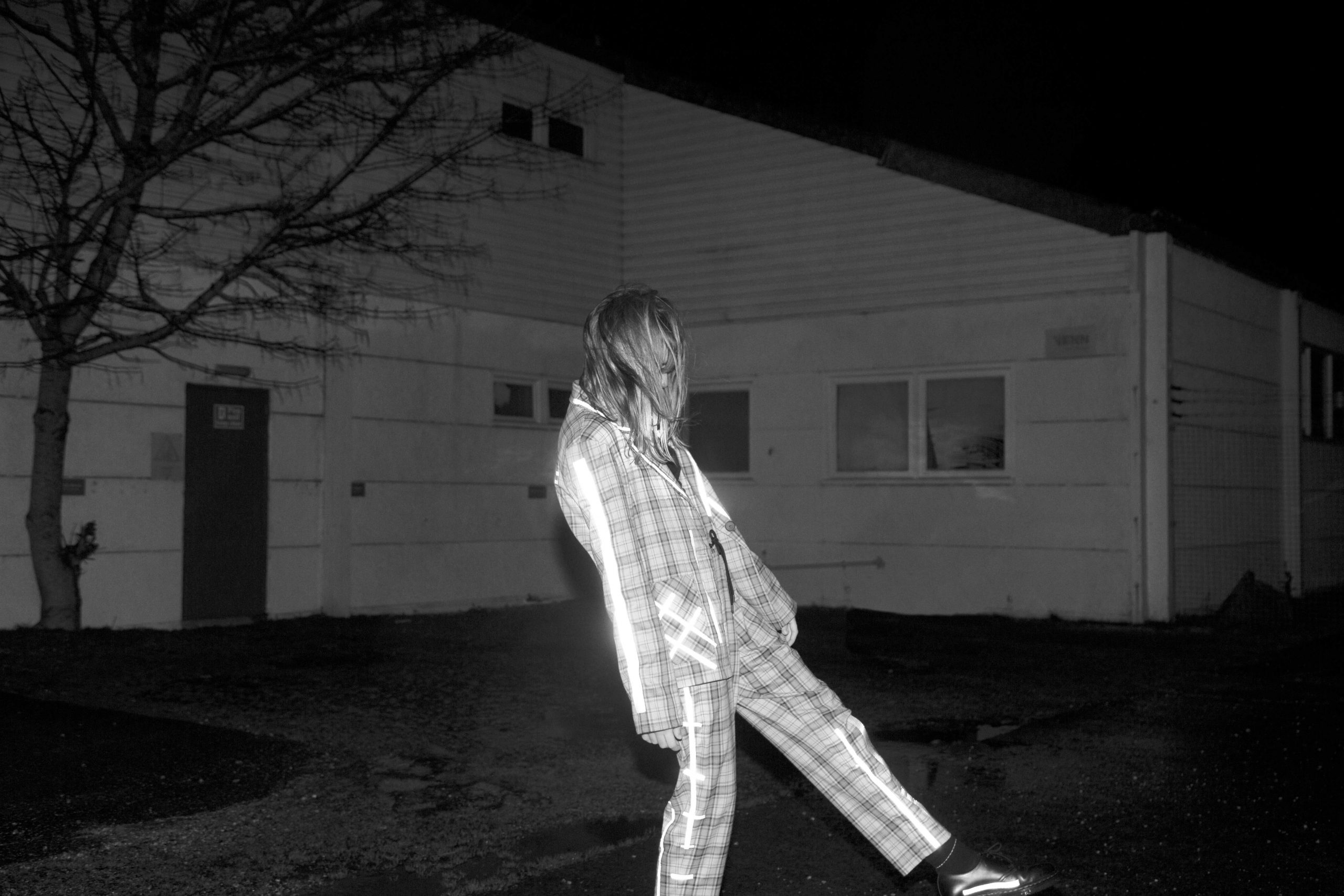 Sophie Preston - Turn and Face the Strange. Illuminated figure jumping over mounds of land, house in background