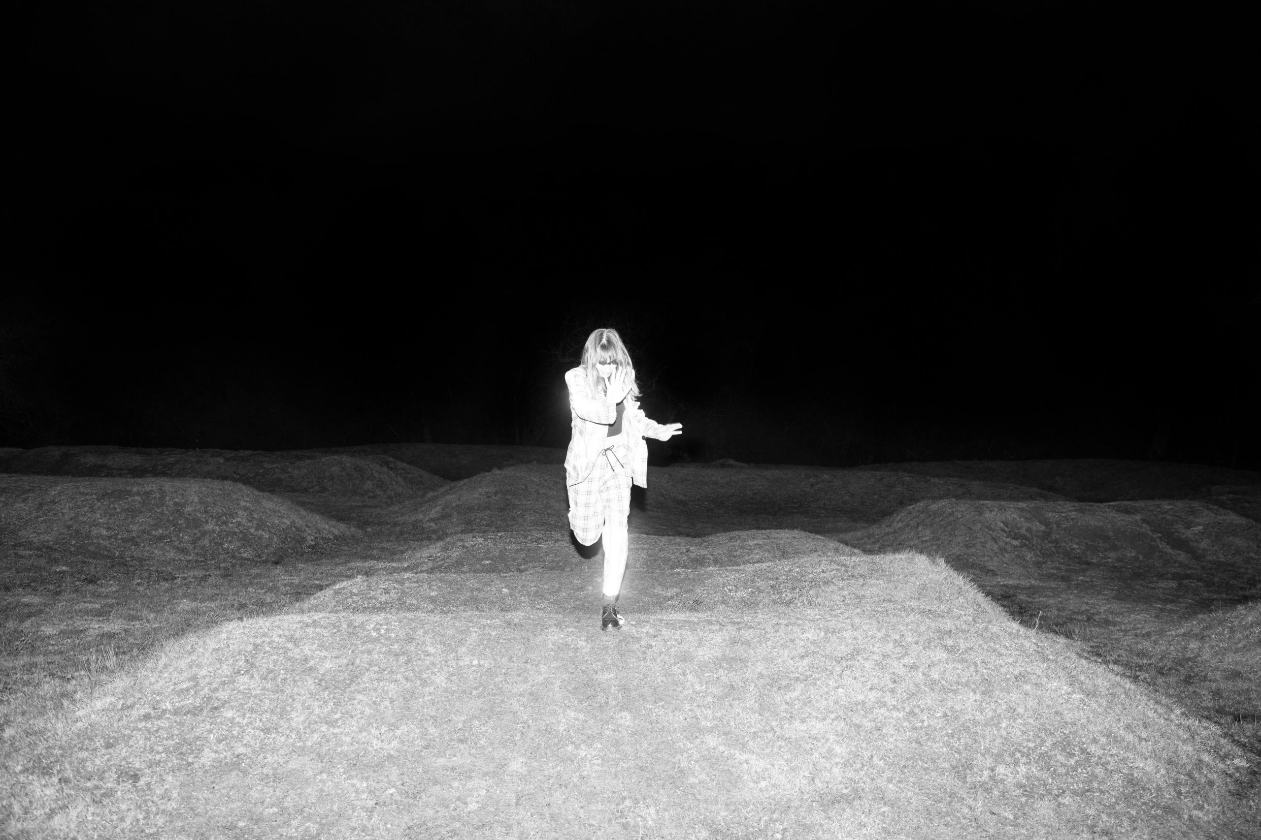 Sophie Preston - Turn and Face the Strange. Illuminated figure jumping over mounds of land